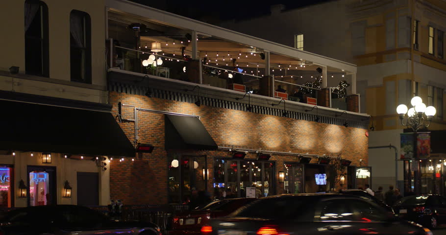 A dusk establishing shot of a typical upscale bar and restaurant in a tourist area of a large city. Red brick facade.
