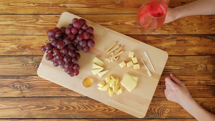 Woman with red wine eating cheese. Grapes and cheese on a wooden table.