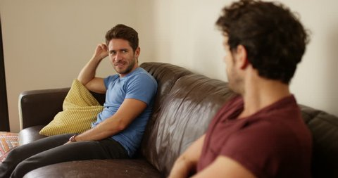 4K Gay couple with relationship problems sitting far apart on the couch while arguing. Slow motion.