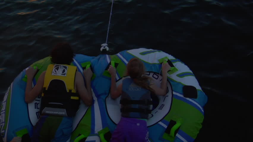 LAKE POWELL, UTAH - CIRCA 2010: kids on inter-tubes pulled by ski boat in the summertime
