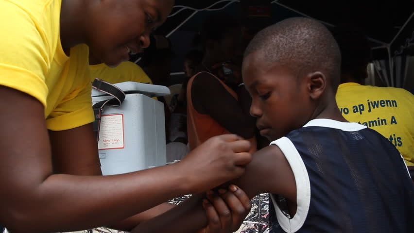 HAITI - CIRCA MAY 2012: young Haitian boy receives vaccination shot in Port-Au-Prince
