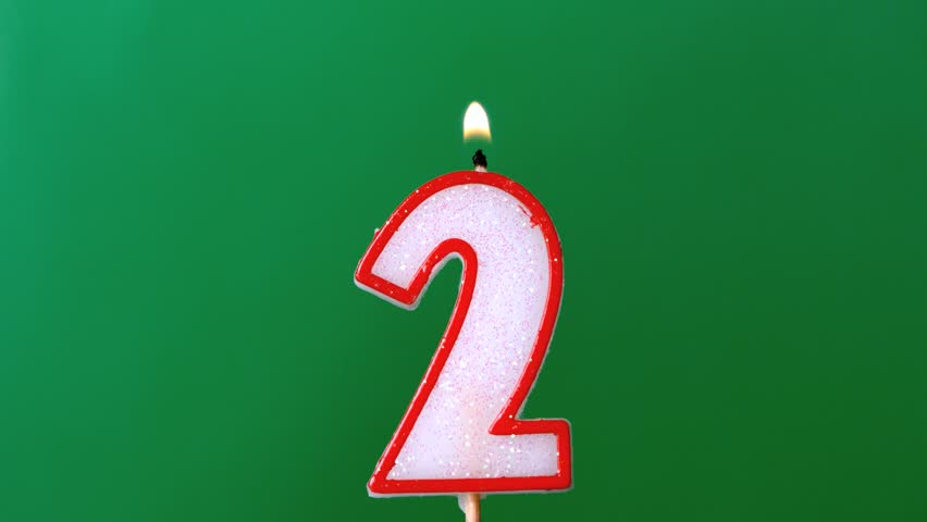 Two birthday candle flickering and extinguishing on green background in slow motion