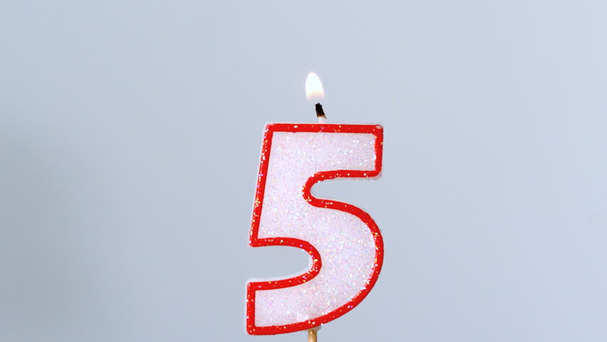 Five birthday candle flickering and extinguishing on blue background in slow motion