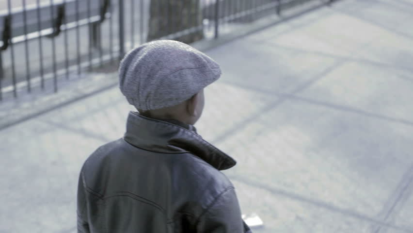 Young African American Kid walking down the street with a black coat and hat