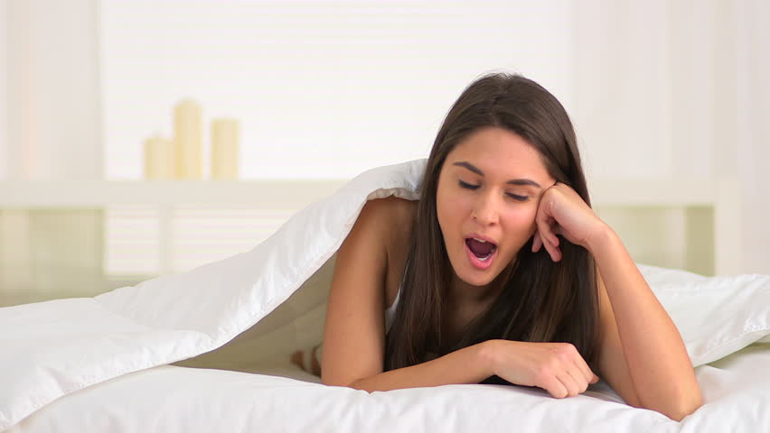 Cute woman yawning in bed