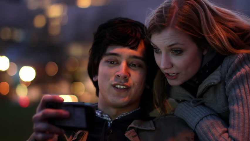 Smart Phone Couple at Night.  Attractive young couple laugh as they find content on a smart phone which illuminates their faces as day turns to night. | Shutterstock HD Video #3561824