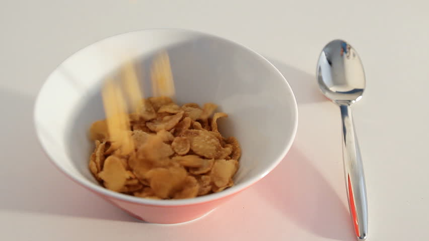 pouring flakes into a breakfast bowl with a spoon beside the bowl on a white table