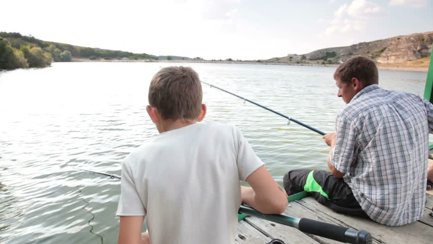 Father and son fishing together by the lake in summer