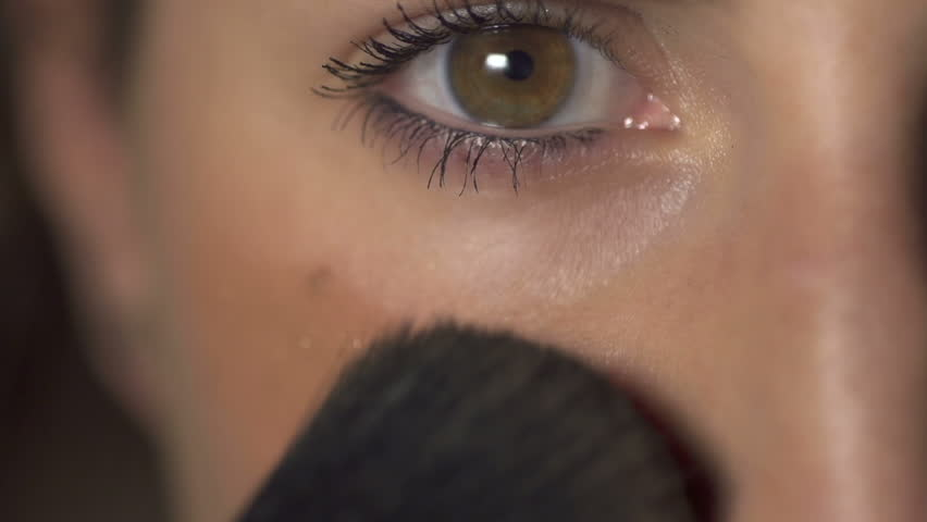 Close-up: young woman putting on makeup. Camera is the mirror.