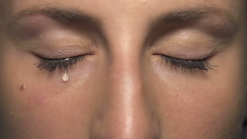 SLOW MOTION CLOSE UP: Tear comes out of an eye and streaks down the cheek. Sad abused female with brown eyes crying