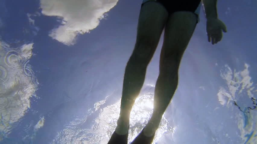 Underwater scene of a swimmer with swim fins against the sun