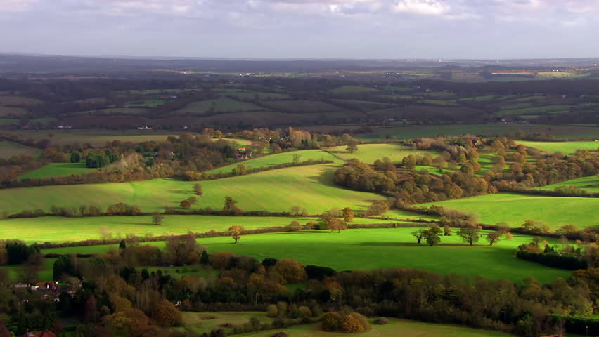 Stunning aerial shot over lush green fields and meadows in the English countryside. It is a clear, bright autumn day and the sun is shining. | Shutterstock HD Video #3588392