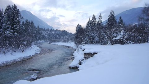 AERIAL: Flying above misty river in winter. Whitewater river snaking through stunning snowy winter landscape. Beautiful snowy winter wonderland.