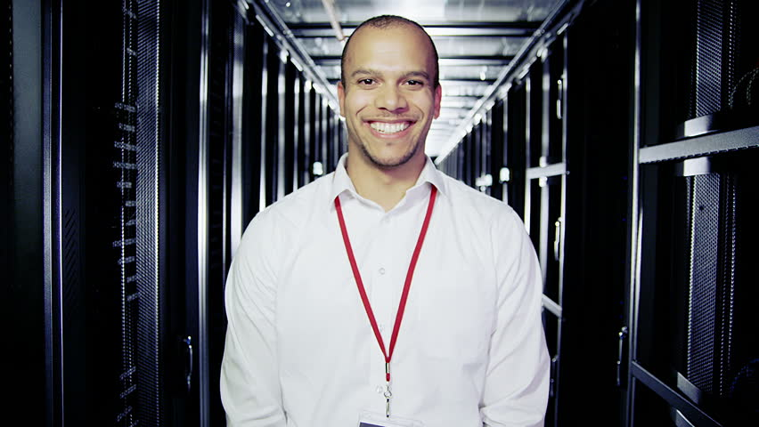 Portrait of a male IT engineer who is working in a data center with rows of server racks and computers.  | Shutterstock HD Video #3589283