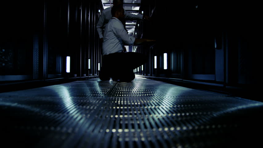 Time lapse of a team of people working in a data center with rows of server racks and super computers. They are looking into data cabinets and checking cables and other equipment.  | Shutterstock HD Video #3589316