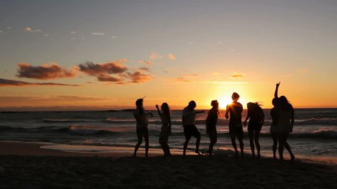 Group Of Young Hipster People dancing At Beach Party on sunset.