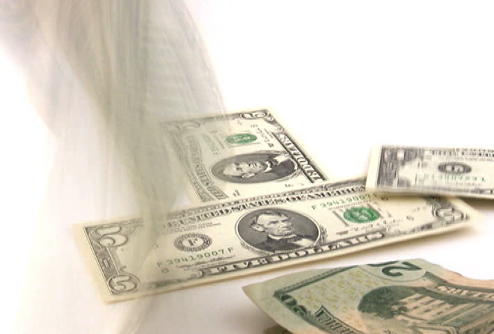 U.S. money falling on a white background.