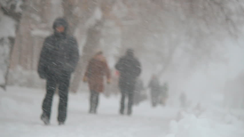 people walking on snowy road. Blizzard, snowfall. Christmas and New Year winter weather.