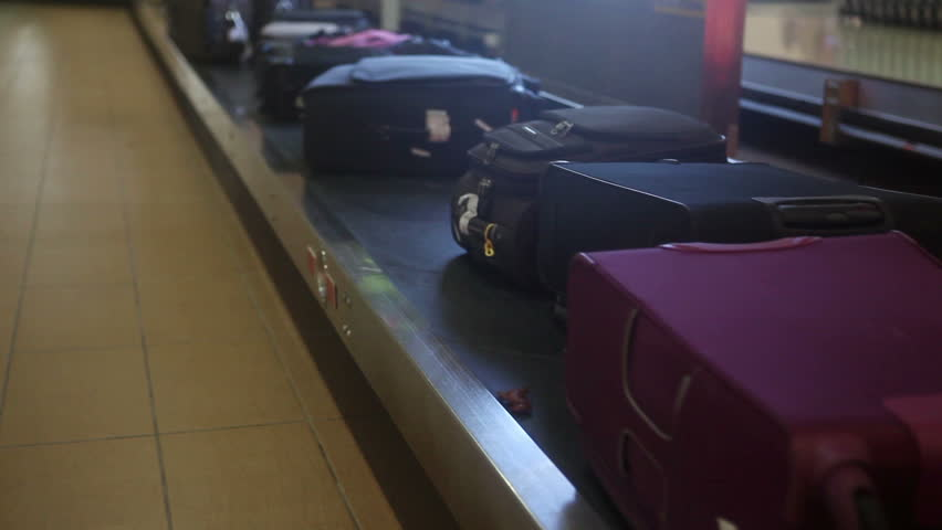 Different luggage on airport conveyor belt