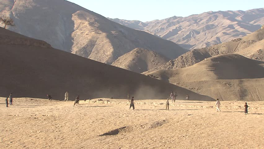 Village in Upper Yaftal, Afghanistan - November 9, 2010: Boys playing soccer/football on a small plateau near a village in north-east Afghanistan.