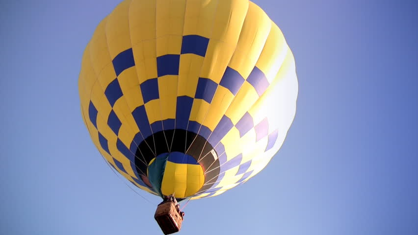 Yellow-blue Hot Air Balloon slowly rises into the blue cloudless sky. In the basket of the Hot Air Balloon are people but their faces are not visible