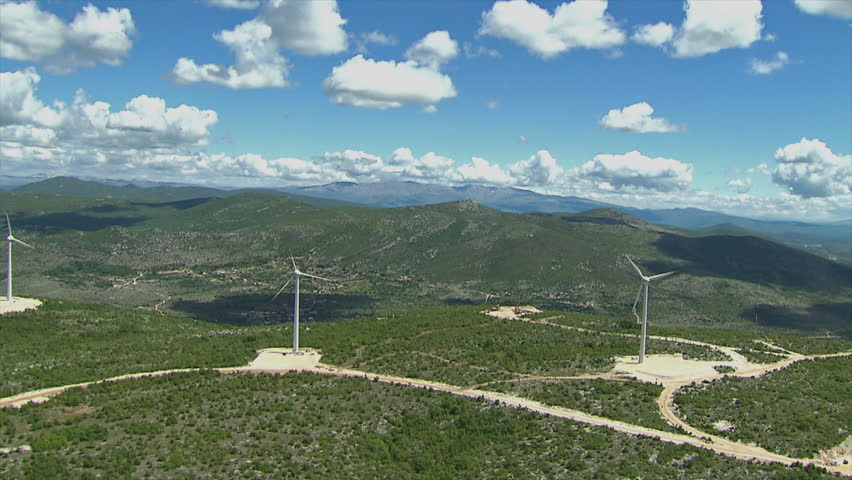 Aerial helicopter shot of wind farm fans