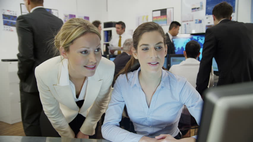 Two attractive female financial traders are working in a busy office filled with computers. They are discussing share prices, as the rest of their team can be seen hard at work in the background.