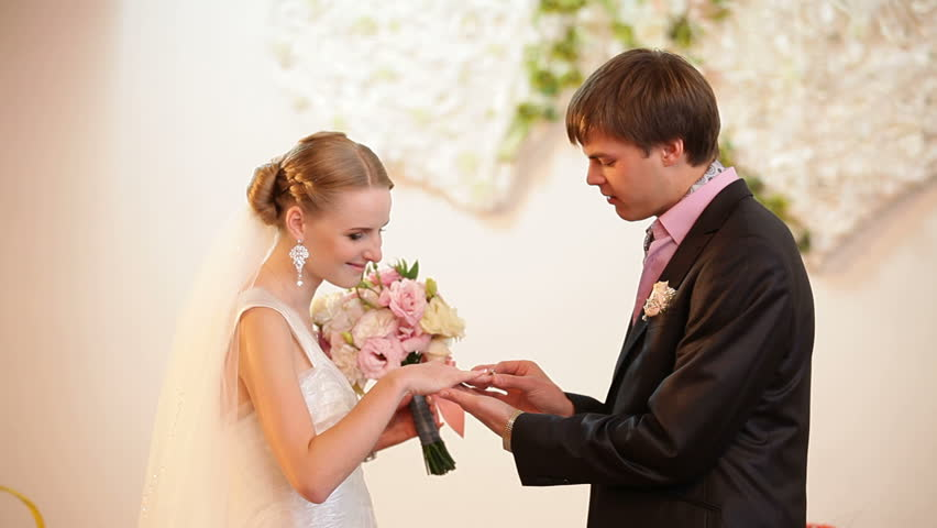 Groom and bride are exchanging wedding rings.