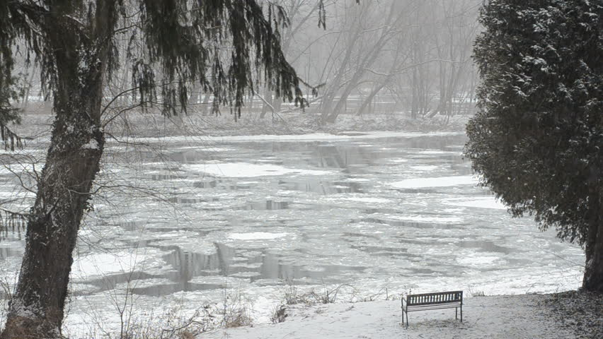 snowing winter scene with ice flowing down river overlooking a bench