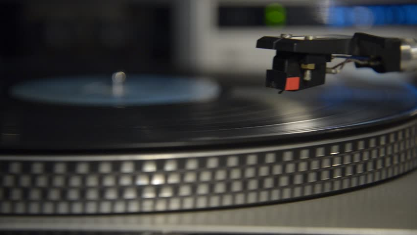 Close up to a turntable. Putting a vinyl record on and off