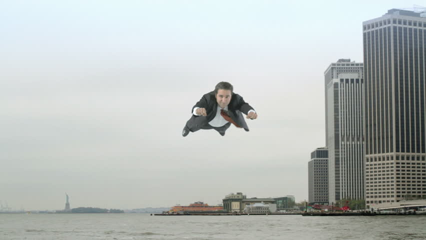 Man in a business suit flies from Manhattan's financial district and along the