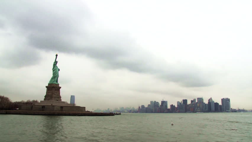 Drifting by the Statue of Liberty on an overcast day, the New York city skyline in the background.