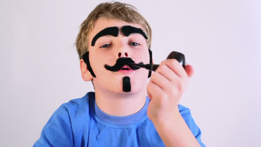 Little boy imitates pipe smoking and he has fake mustache, eyebrows, beard and sideburns