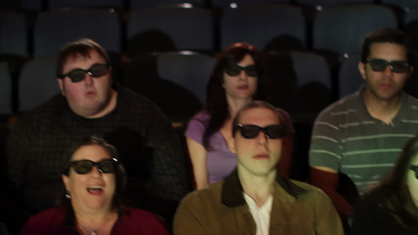 Audience reaction with emphasis on man at 3D movie screening. Camera moves on a jib and moving images are projected on the people.
