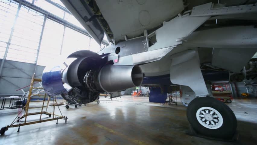Disassembled turbine of aircraft under repair in hangar, panorama