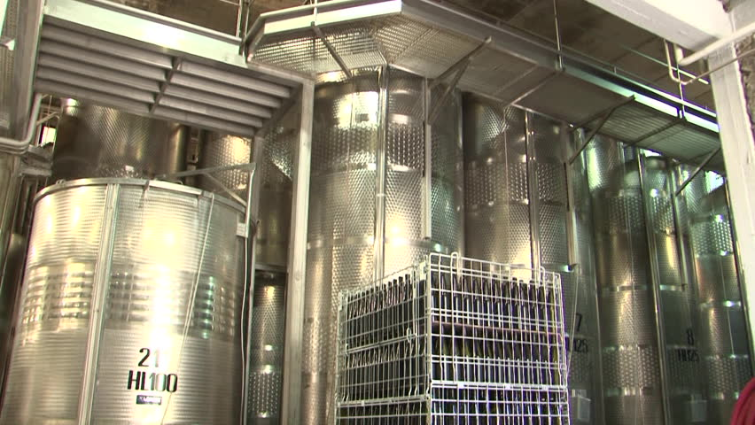 Crates of empty wine bottles and stainless steel distilling vats at a winery