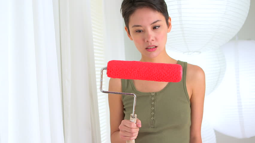 Angry Asian woman with paint roller in hand