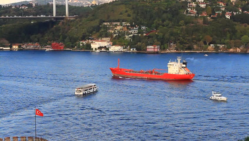 Bosporus seascape with a cargo ship, tour boat and a leisure craft. Red