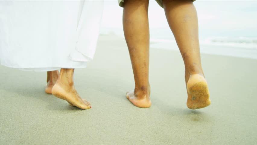 close up legs feet caucasian parents daughters walking barefoot wet