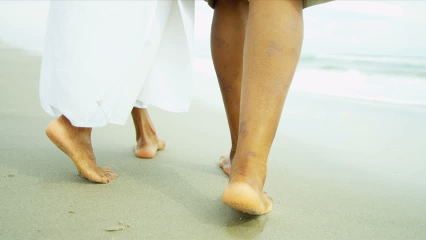 lower body shot legs of mature african american couple walking wet