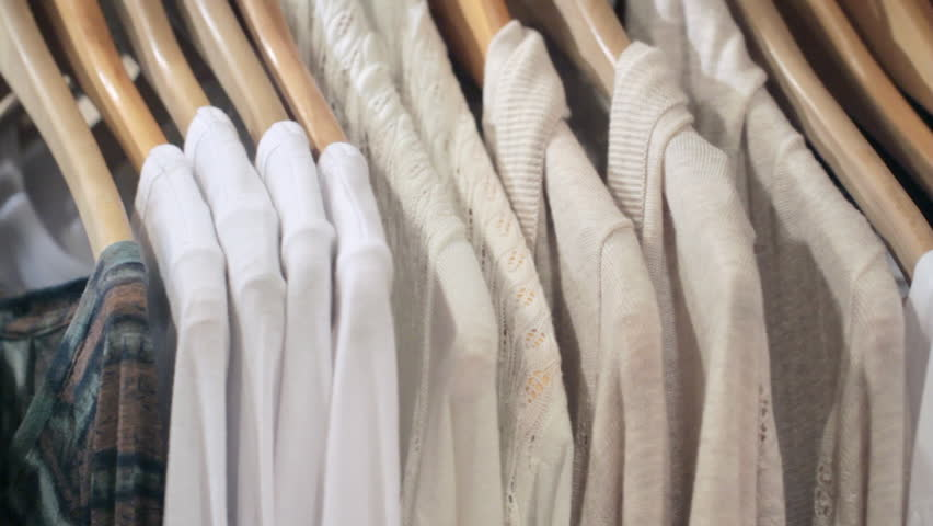 Woman's hands run across a rack of clothes, browsing in a boutique. Dolly shot
