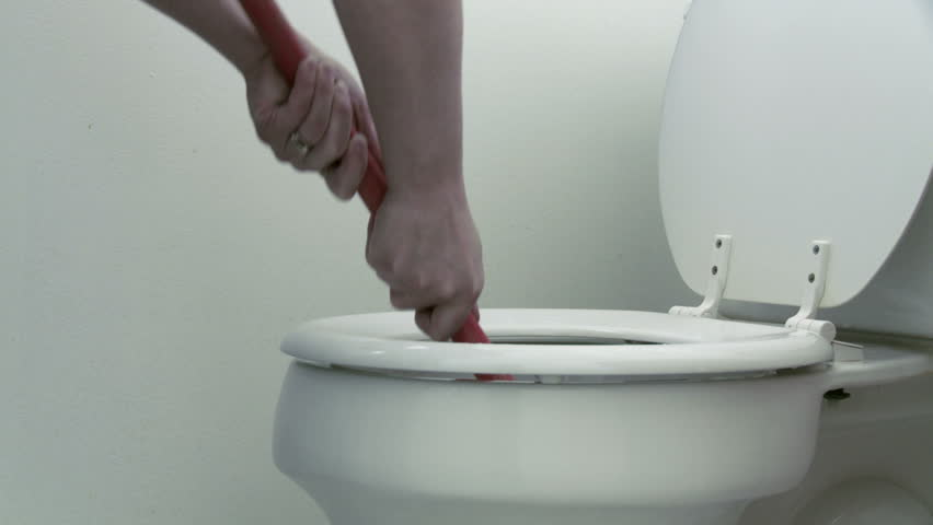 Using a plunger in an attempt to unclog a toilet. Dolly move in this clip.