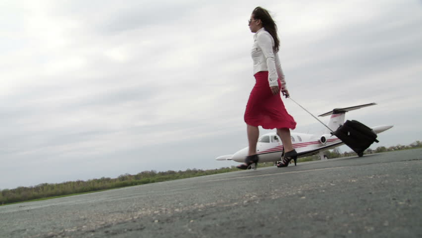 Attractive girl wearing a red dress and white jacket, walks with her suitcase across a runway in front of an executive jet. Wide shot, canted camera, slow motion recorded at 60fps.