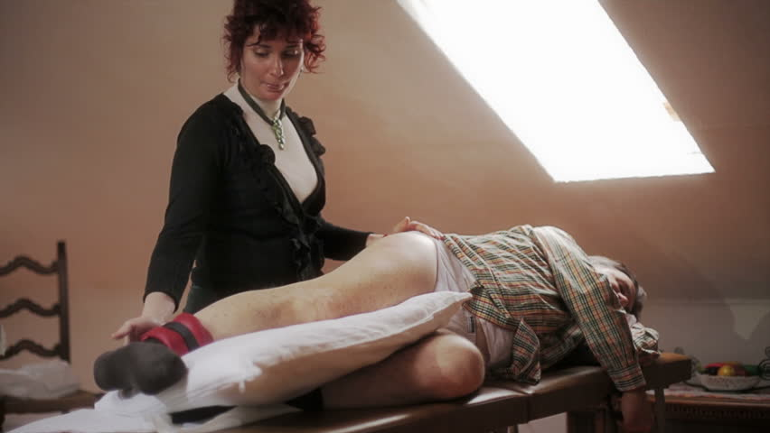 Masseuse elevates the straight leg of a patient in physiotherapy