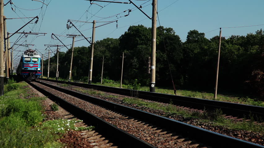 Summer. Sunny weather. Railroad tracks in the woods. The passenger train travels