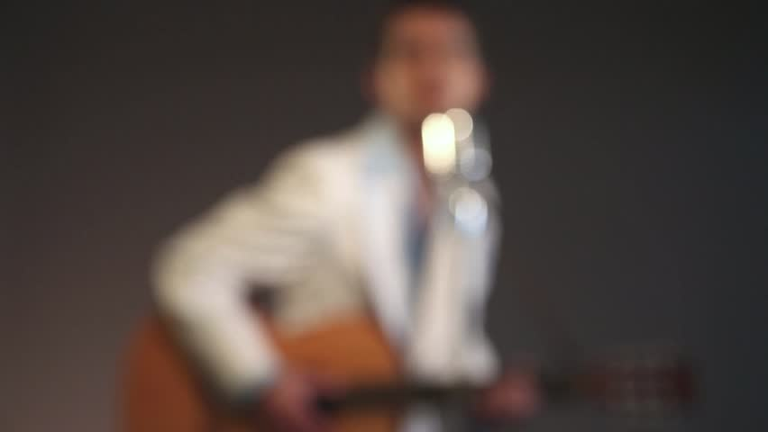 Retro rockabilly musician playing acoustic guitar and singing. Wearing white suit with blue shirt. Studio shot. Starting and ending blurred. (No audio).