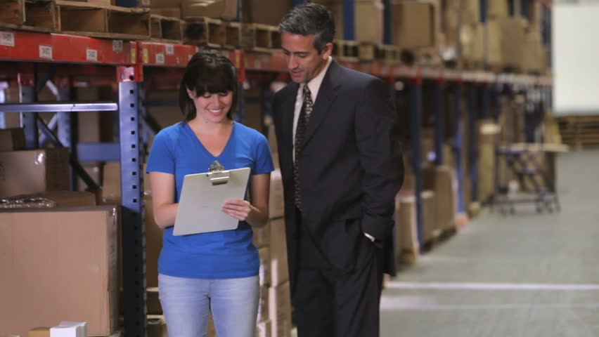 Manager walking in warehouse, talks with worker checking goods on clipboard and then walks away. Shot on Canon 5d Mk2 with a frame rate of 30fps