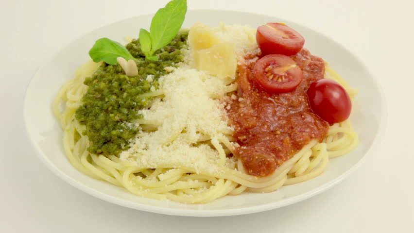 On a white plate rotates pasta. On top of pasta - Pesto, Parmesan and Tomato sauce - in the national colors of the Italian flag