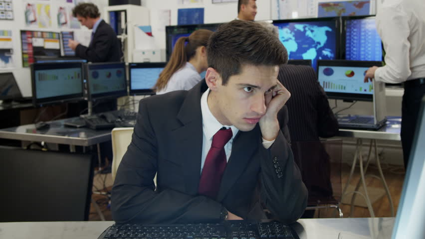 A very bored and tired  young businessman is struggling to stay awake at his desk while he is at work. As he lapses into sleep he looks around to check that his colleagues haven't noticed.