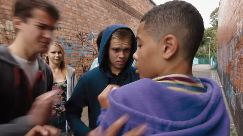 Teen bullying - a group of teenagers attack one boy